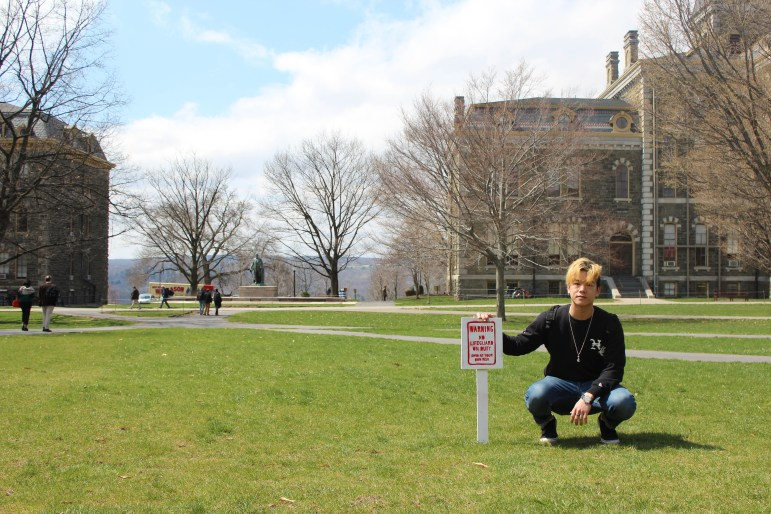 "Daniel Seung Hwan Lee '20 crouches next to his art installation, the ""Cornell Beach,"" after the other sign he created was swiped earlier in April."