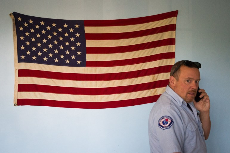 George Tamborelle, chief of the Cayuga Heights Fire Department takes a call in the bunker common room on Monday.
