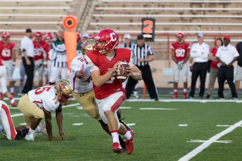 Quarterback Connor Ostrander rolls out for a pass Friday against Caldwell. The junior had 99 throwing yards and 63 rushing.