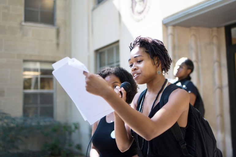 Delmar Fears '19, front, and Traciann Celestin '19, co-chairs of Black Students United, read from a list of 12 demands to Cornell before delivering the list to President Martha E. Pollack in Day Hall
