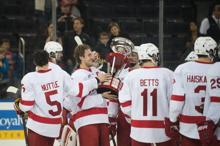 Senior captain and forward Alex Rauter (center) carries the Kelly-Harnkess Cup as he and his teammate celebrate their first win over BU at MSG.