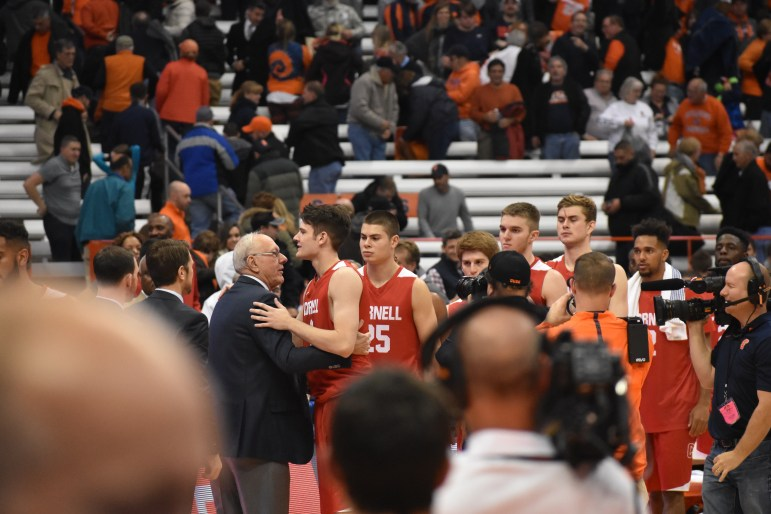 Cornell freshman forward embraces his father, Syracuse head coach Jim Boeheim, after the 77-45 Orange win Saturday night.