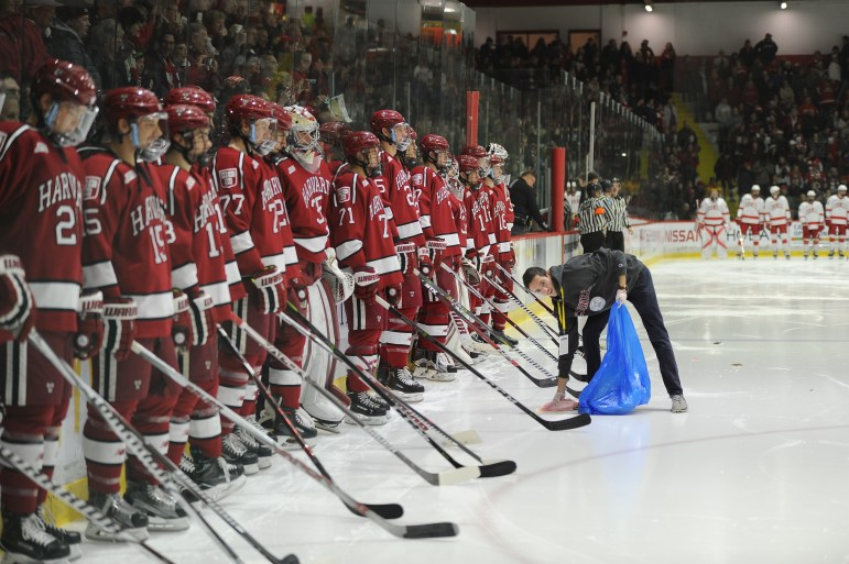 A rink attendant collects fish in front of Harvard players before the start of the Ice Hockey game on Saturday night. (Corinne Kenwood / Sun Staff Photographer)