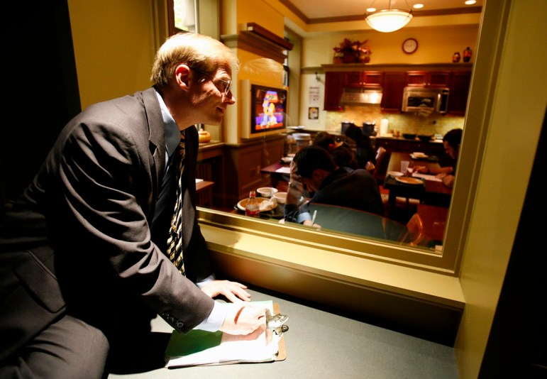 Using a one-way window at the Cornell Food and Brand Laboratory, director Brian Wansink keeps an eye on students taking part in an eating behavior study in October 2006.