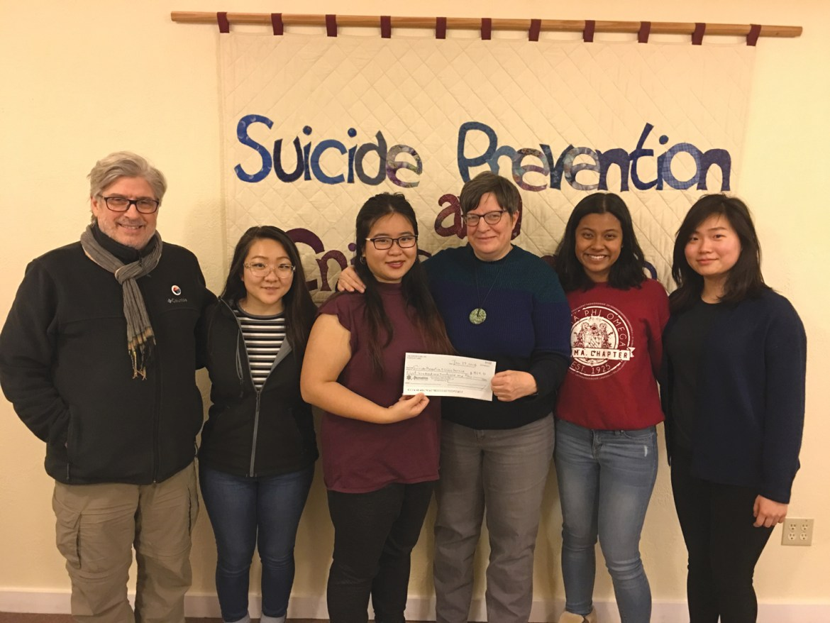 Alpha Phi Omega President Winnie Ho hands a check to executive director Lee-Ellen Marvin of the Suicide Prevention and Service in a ceremony last Wednesday.