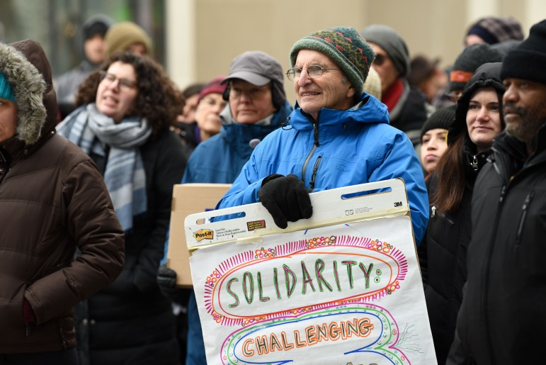 """Protestors wore """"RESIST"""" buttons and held """"SOLIDARITY"""" posters to support marginalized groups in the community."""