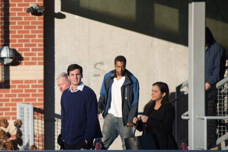 John Greenwood '20 walks out of the Ithaca City Court with his attorneys in November of 2017.