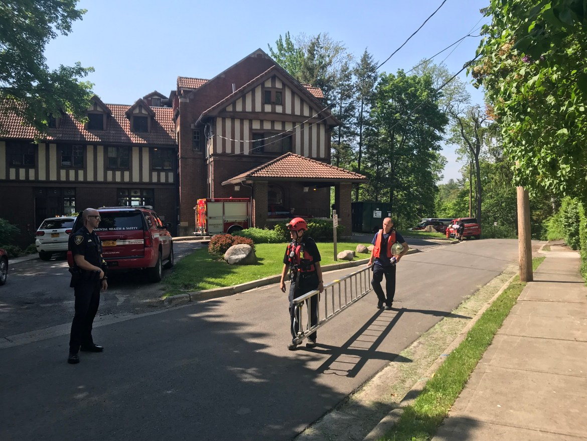 Emergency personnel carry a ladder away from the scene on Willard Way after helping with the recovery of a body in Fall Creek Gorge on Friday afternoon.