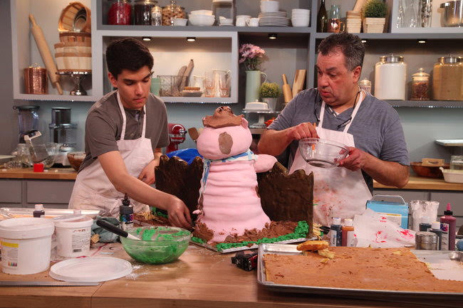 Juan Lopez Jr. '22 and his father put finishing touches on their cake during the baking competition.