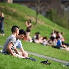 Students gather on Libe Slope to relax on a sunny afternoon.