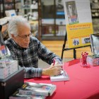 Steve Nelson '62 signs copies of his book at the Cornell Store.