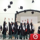2016 graduates of the Cornell Prison Education Program throw their caps in the air after receiving their degrees.