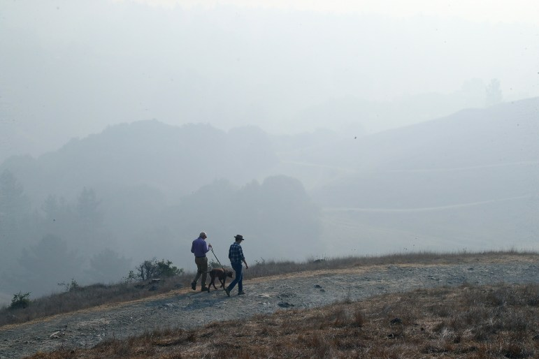 Smoke from the Camp Fire lingers over Oakland Hills as people walk their dog in Oakland, California on Nov. 15.
