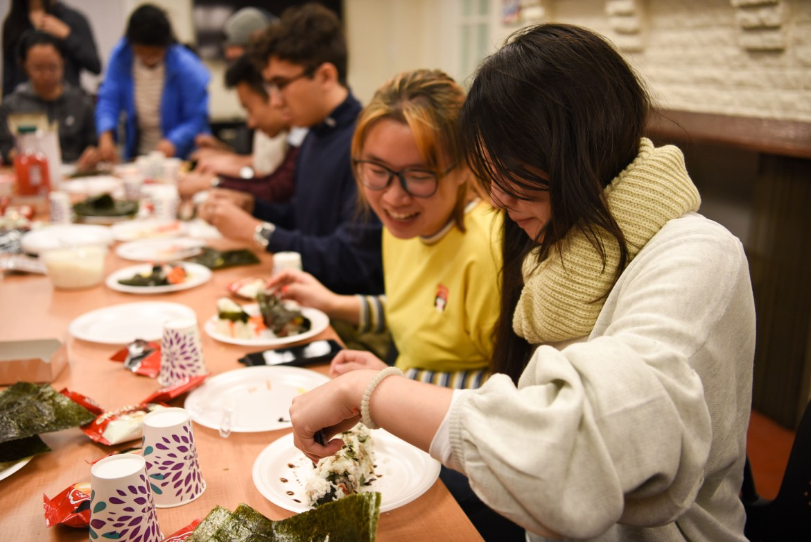 Community members create dishes during the Asian Chopped culinary competition.