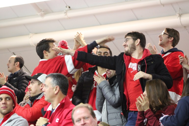 """Cornell fans at """"Lynah East"""" celebrate the first goal in the win over Harvard."""