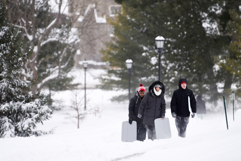 Cornellians walk up the slope carrying sleds on Jan. 20, 2019.