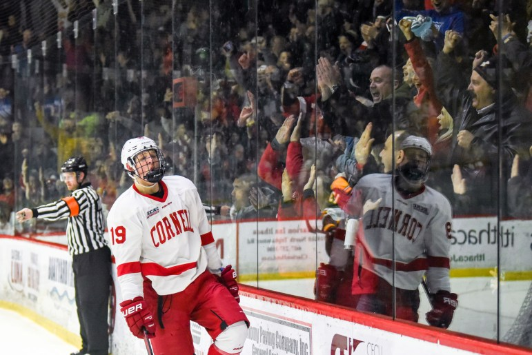 Fans pound the glass as freshman forward Michael Regush celebrates his goal over Clarkson on Friday. The Red went on to win the top-10 matchup 5-0. (Boris Tsang / Sun Assistant Photography Editor)