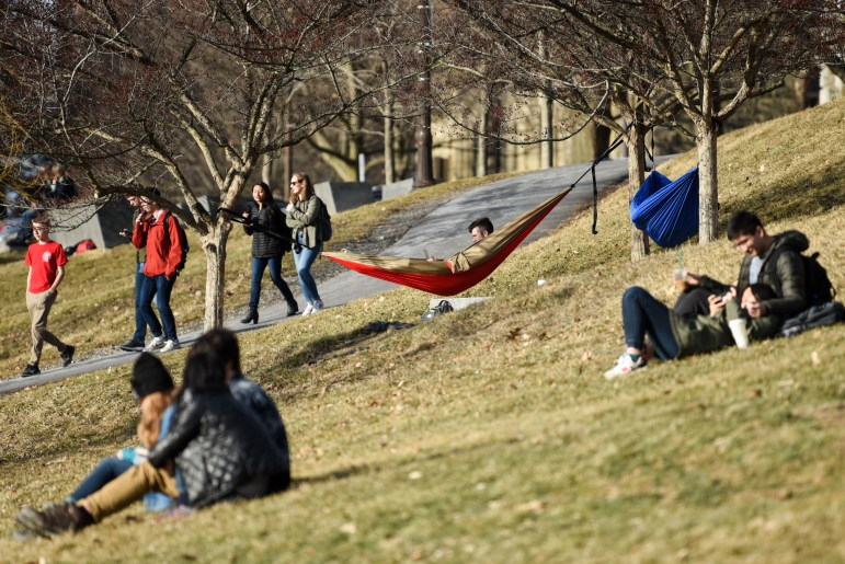 Students relaxed on Libe Slope as temperatures rose above 50 degrees on Friday. (Boris Tsang / Sun Photography Editor)