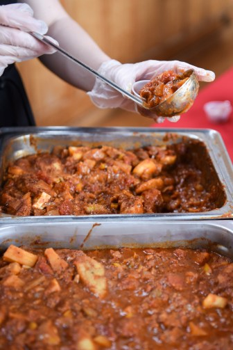 A volunteer scoops chili at the cook-off.