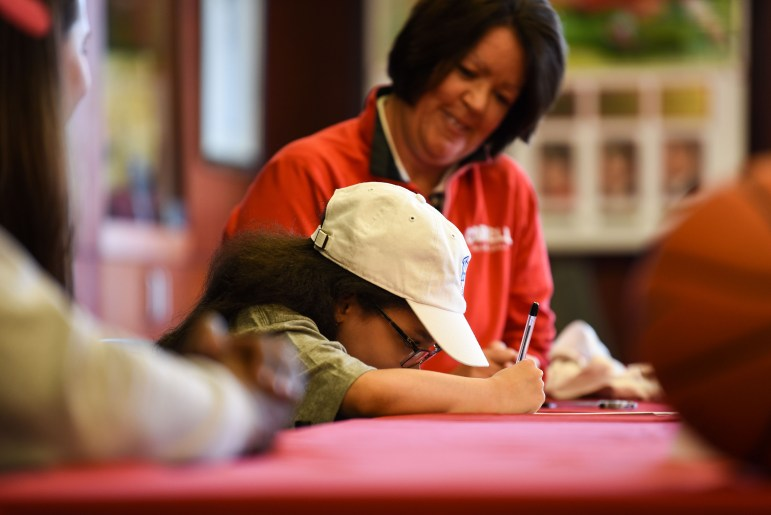 """Karina Hill signs her """"letter of intent"""" as Cornell head coach Dayna Smith looks on."""