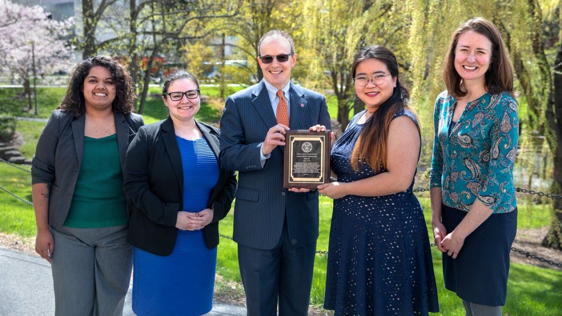 Winnie Ho '19 stands by a few of her collaborators from Engaged Cornell and  the New York Drug Policy Alliance as Joel Malina, vice president for university relations, presents her with the 2019 Campus-Community Leadership Award.