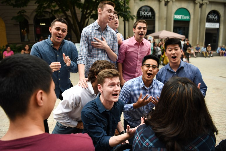The Men of Last Call serenade an audience member during C.U. Downtown at the Ithaca Commons on Saturday. (Boris Tsang/Sun Photography Editor)