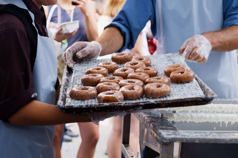 A tray of freshly baked cider donuts makes its way to the customers. (Michael Suguitan/Sun Staff Photographer)