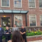 Acting Police Chief Dennis Nayor briefs the press with other public officials in front of City Hall.