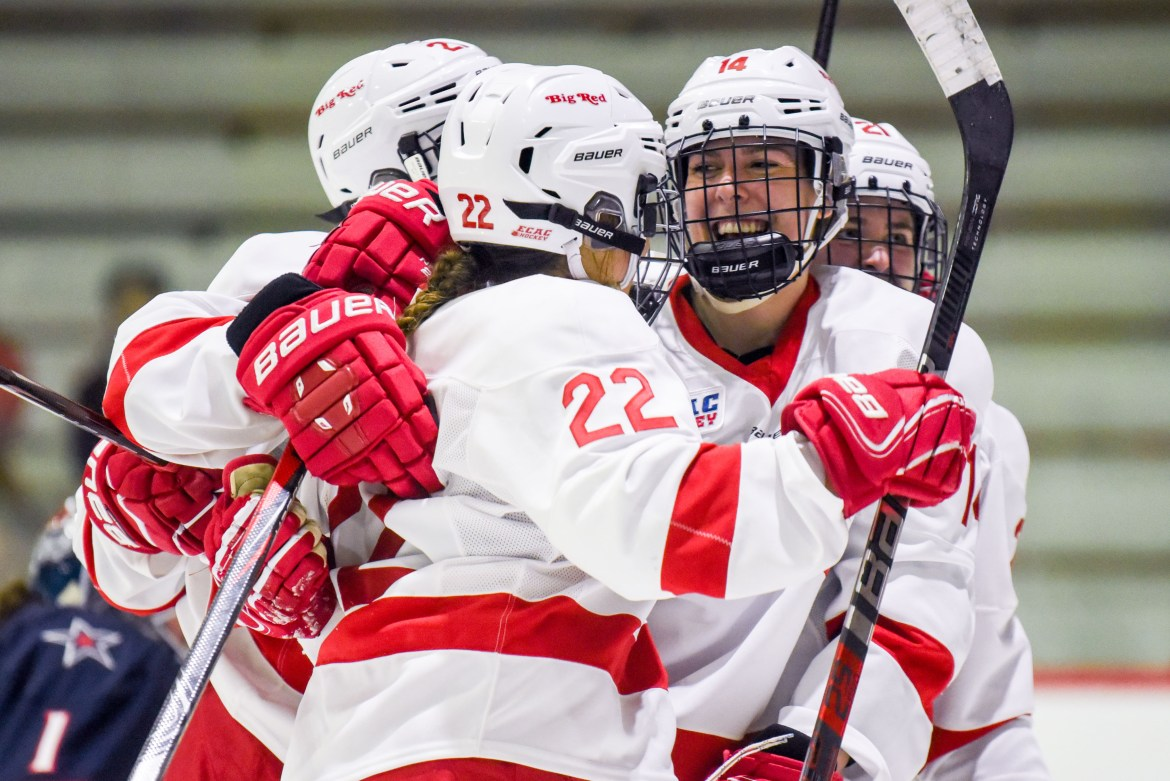 Junior forward Maddie Mills, center, celebrates with senior defenseman Jaime Bourbonnais, right, after scoring a goal to put the Red up 2-0 in the second period of Friday's game.