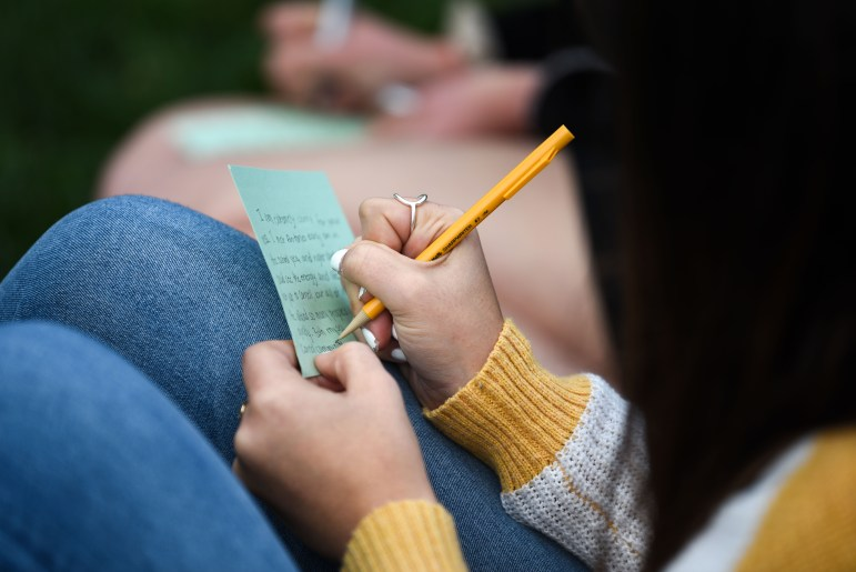 Students write letters to the family of Antonio Tsialas '23 on note cards outside Anabel Taylor Hall during the service of remembrance on October 29th, 2019.