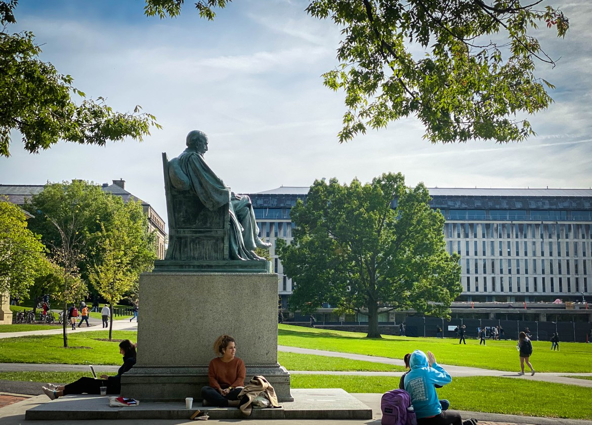 Students sit around a statue of A.D. White in the Arts Quad on Oct. 17, 2019.