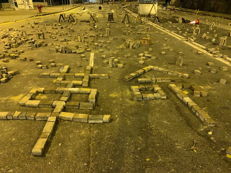 """Protestors at University of Hong Kong spell out """"revolution"""" in Chinese with roadblocking bricks."""
