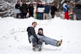 Michelle DeSouza '22, left, and Rianna Thomas '22 slide down the slope in a laundry bin during the snow day on December 2nd, 2019.