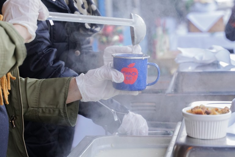 A visitor receives a cup of warm chowder at the booth in front of the Mahogany Grill at the 10th Annual Chowder Cook-Off on Saturday. (Michelle Zhiqing Yang / Sun Staff Photographer)