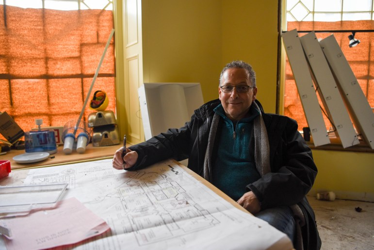 Owner Gregar Brous sits in front of the demolition plan for the new Collegetown Bagels location at Sheldon Court on Sunday. The current location on College Avenue will be demolished in June. (Boris Tsang/Sun Photography Editor)