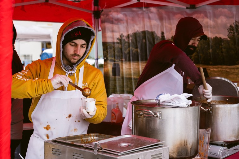 Ithaca Beer Co. employees scoop chili into sample cups at the 22nd annual Chili Cook-Off in the Ithaca Commons. On Saturday the family-friendly festival attracted more than 30 restaurants ready to compete for the ultimate chili recipe. (Ashley He/Sun Staff Photographer)