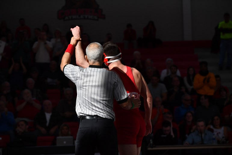 A Cornell wrestler raises his arm, declaring his victory at the dual against Binghamton on Saturday. The Red claimed a 32-8 victory, bringing its current record to 10-6 overall. (Ben Parker/Sun Assistant Photography Editor)