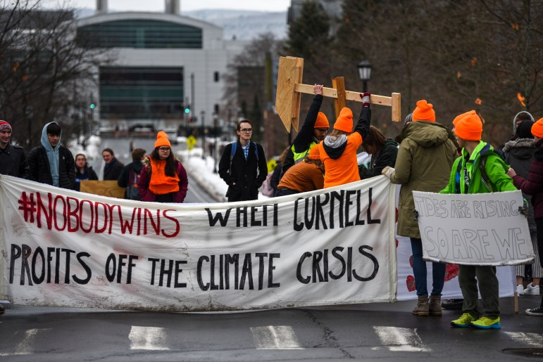 Donning orange hats and vibrant clothing, Cornellians gathered to call for Cornell to divest in fossil fuels. Climate Justice Cornell protesters assembled at the intersection of Tower Road and East Avenue on Thursday. (Boris Tsang/Sun Photography Editor)