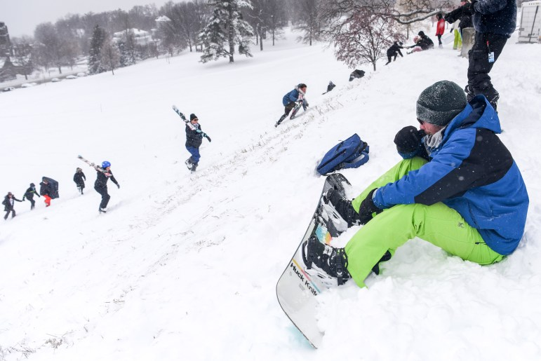 During the snow day, a student waits at the top of Libe Slope, waiting to speed down with a snowboard. Students make their way up Libe Slope after classes were cancelled and the Ithaca campus was closed on Friday. (Boris Tsang/Sun Photography Editor)
