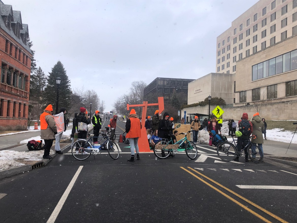 Protestors with Climate Justice Cornell blocked sidewalk outside Statler Hall Wednesday, forcing the closure of a section of East Avenue.