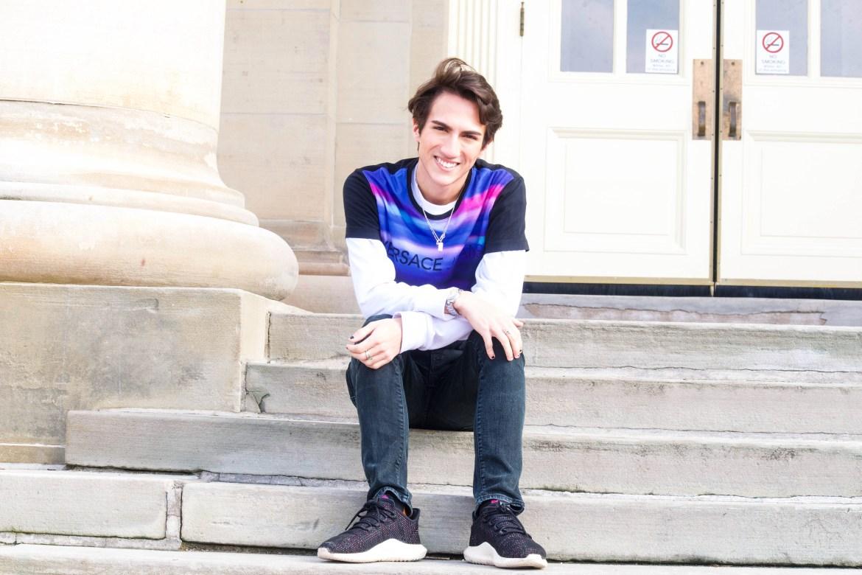 John Dombrowski '23 with 1.1 million TikTok followers, sits on the stairs of Goldwin Smith Hall.