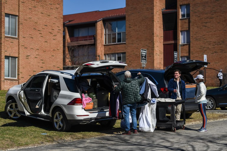 Students load their cars at the parking lot behind Ujamaa Residential College on Saturday. North Campus filled with cars and parents following President Pollack's announcement that classes will be suspended until April 6 because of COVID-19. (Boris Tsang / Sun Photography Editor)