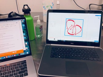 A laptop shows the design for a visor to be 3D printed.