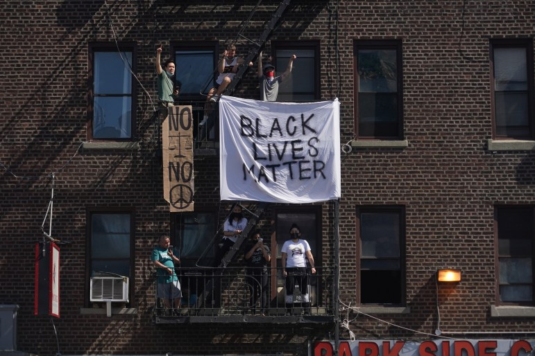 Onlookers hang signs from a building's fire escape as demonstrators crowd a nearby intersection as they protest the death of George Floyd and police brutality on May 30 in New York City.