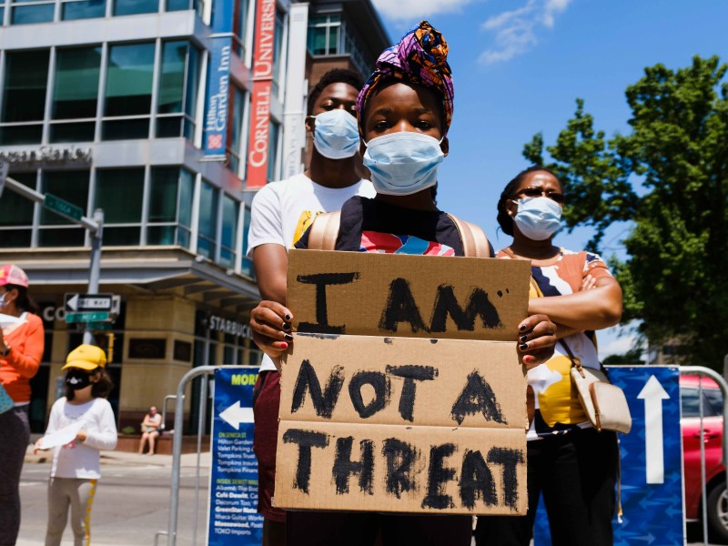 Donning a mask, a child holds up a cardboard sign that reads 'I Am Not a Threat' during the Uplift and Speak Out! rally on Friday at the Ithaca Commons. (Michael Suguitan / Sun Staff Photographer).