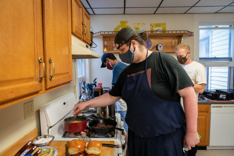 Bobby works on some burgers and noodles at the stove. (Ben Parker/Sun Assistant Photography Editor)