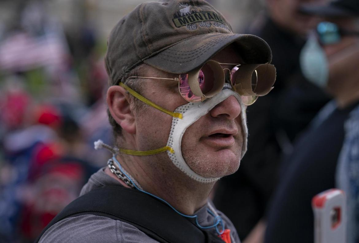 A demonstrator wears a face mask with the center removed while protesting Washington Gov. Jay Inslee's 'Stay Home, Stay Healthy' emergency order outside the Capitol Building in Olympia, Wash., April 19, 2020.