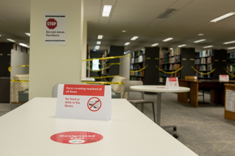 Cornell's campus is full of mask-wearing and social distancing reminders, like this sign in Mann Library.