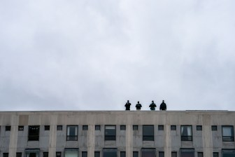 Police officers on the rooftop of a building overlooking the commons