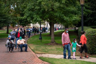 Voters stand and sit in line for early voting on Monday morning, Oct. 12, 2020, at Agnes Scott College in Decatur, Ga.